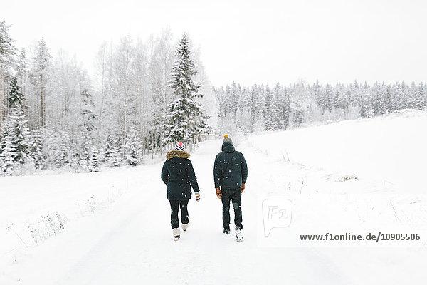 Finnland  Jyvaskyla  Saakoski  Junges Paar  das auf einer schneebedeckten Straße geht.