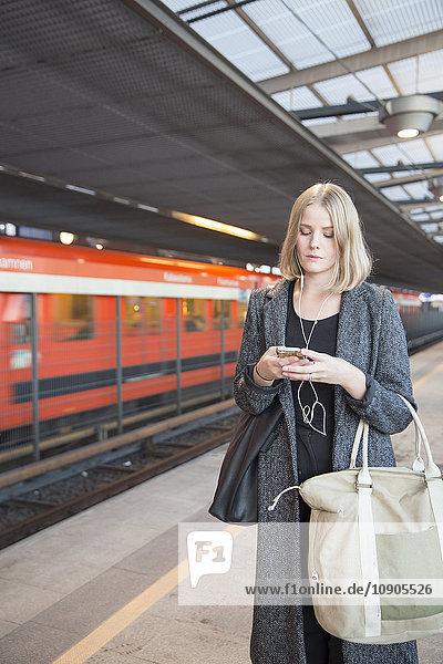 Finnland  Uusimaa  Helsinki  Junge Frau mit Smartphone in der Metro Helsinki