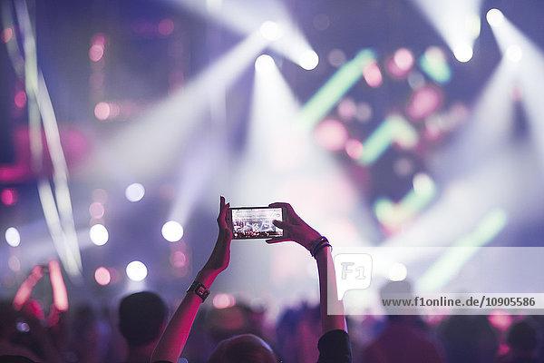 Finnland  Uusimaa  Helsinki  Frau mit Smartphone im Konzert