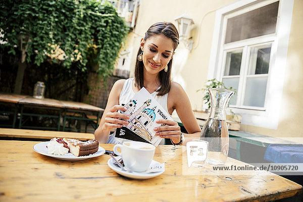 Austria  Vienna  Young woman sitting in Heurigen restaurant writing postcards
