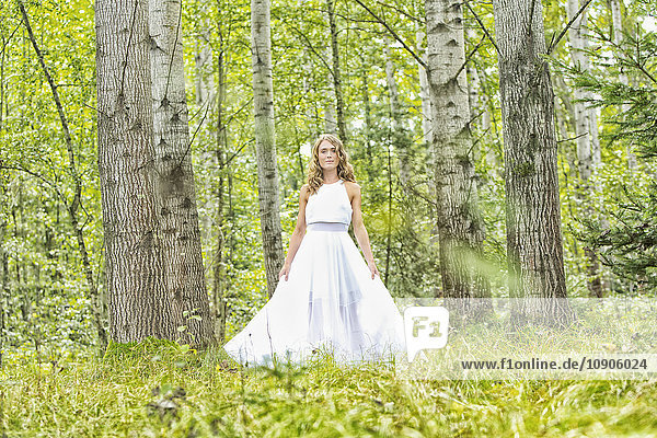 Portrait of young woman wearing white dress in the forest