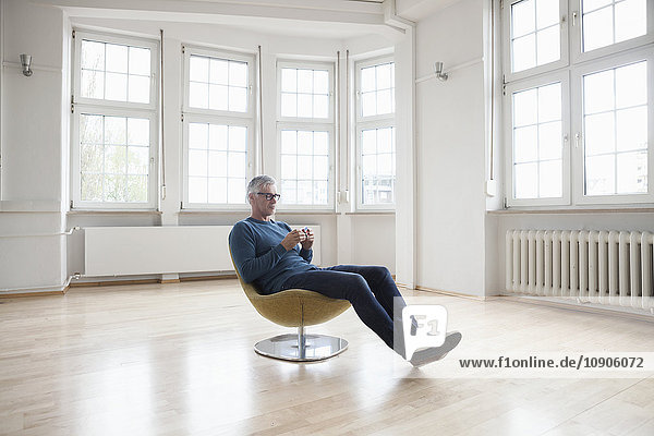 Man sitting in armchair in empty apartment with Rubik's cube