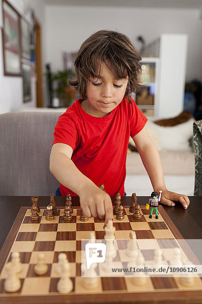 Little boy playing chess at home