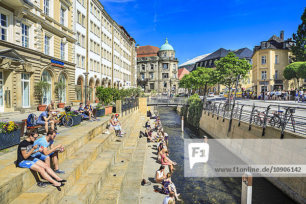 Germany  Bavaria  Bayreuth  people sitting on steps at canal in summer