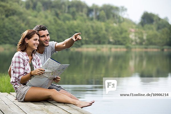 Relaxed young couple with map sitting on a jetty at lake watching something