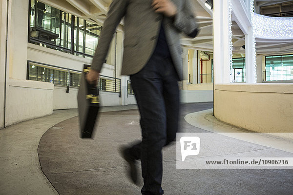 Businessman running on driveway of builing in a hurry
