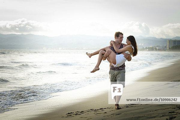 Mann trägt seine Freundin am Strand.