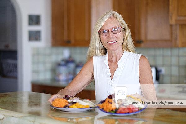 Portrait of smiling senior woman serving healthy food