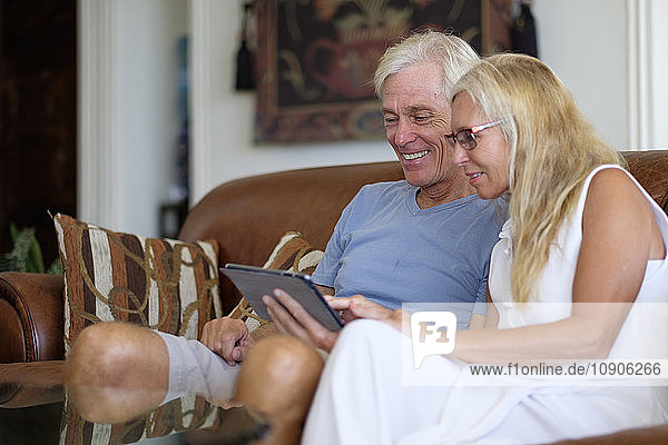 Senior couple sharing digital tablet on couch