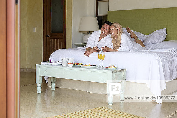 Happy couple in bathrobes lying on bed