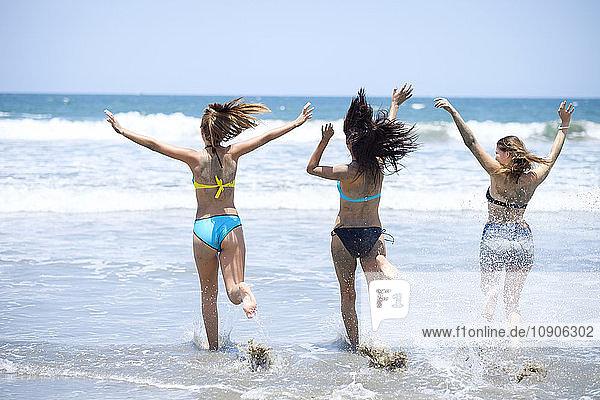 Three friends running in the sea