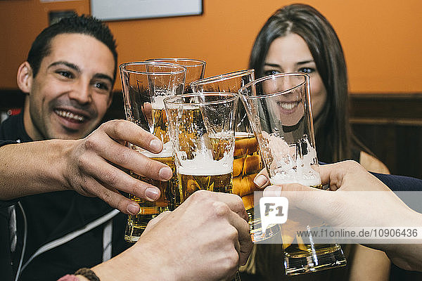 Friends toasting with glasses of beer in a bar