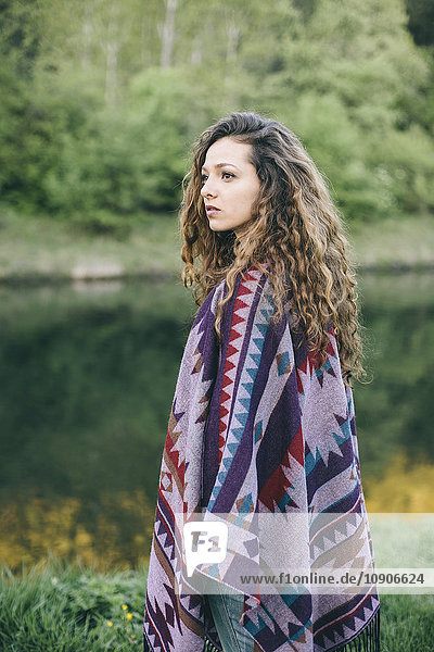 Portrait of young woman wearing patterned poncho