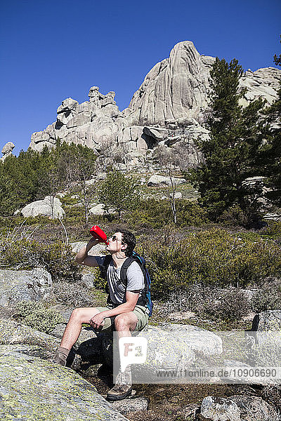 Spain  hiker with sunglasses and backpack drinking from bottle sitting on a rock in La Pedriza
