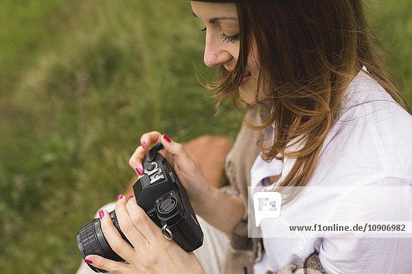 Frau mit einer alten Kamera auf einer Wiese