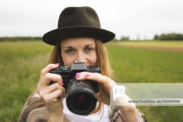 Porträt einer Frau mit Kamera in der Natur