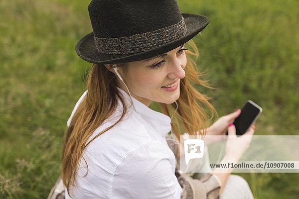 Junge Frau auf der Wiese beim Musikhören mit Kopfhörer und Smartphone