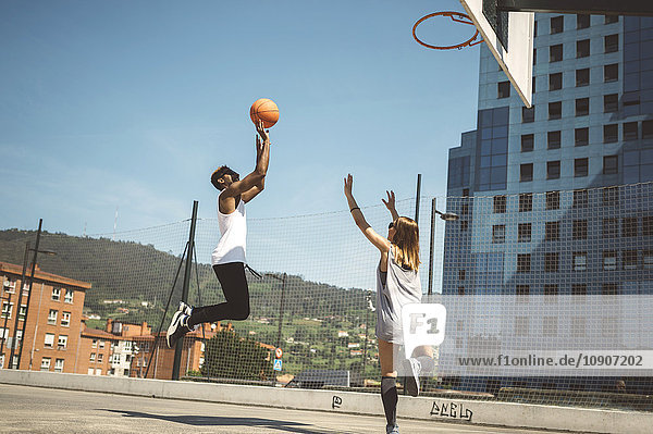 Junges Paar spielt Basketball auf dem Platz