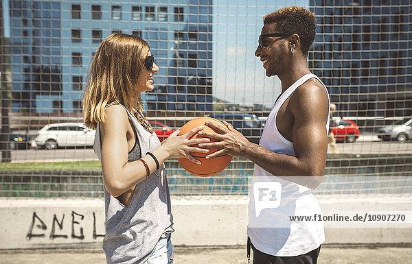 Junges Paar hält Basketball