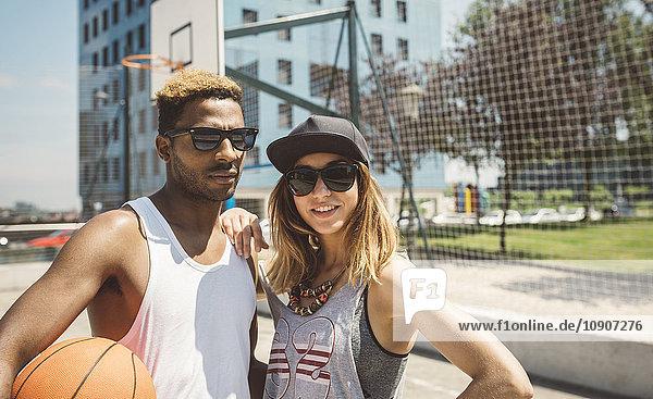 Junges Paar steht auf dem Basketballfeld und schaut in die Kamera.