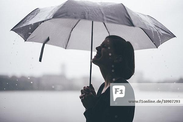 Lachende Frau mit Regenschirm an einem regnerischen Tag