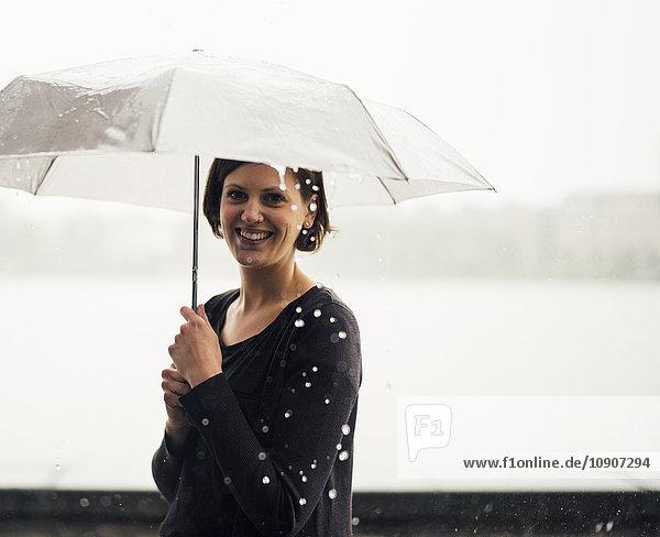 Porträt einer lächelnden Frau mit Regenschirm an einem regnerischen Tag