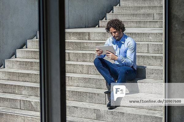 Geschäftsmann sitzt auf einer Treppe und schaut auf die Tafel.