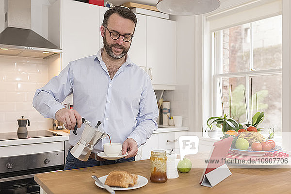 Portrait of man in kitchen pouring espresso into a cup