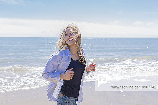 Portrait of smiling young woman running at seaside
