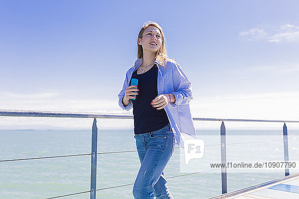 Woman with smartphone on jetty