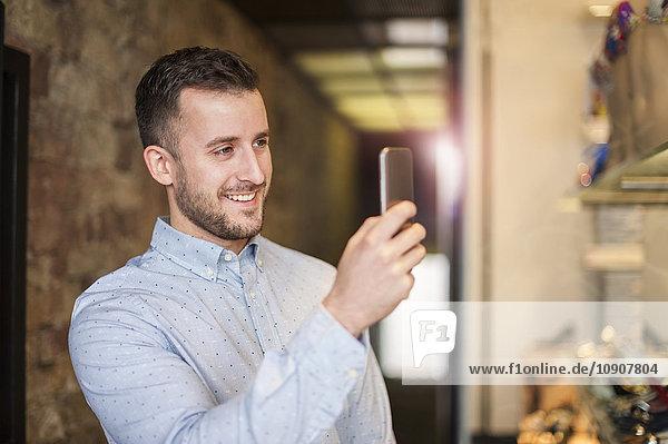 Lächelnder junger Mann beim Fotografieren eines Handys in einem Geschäft