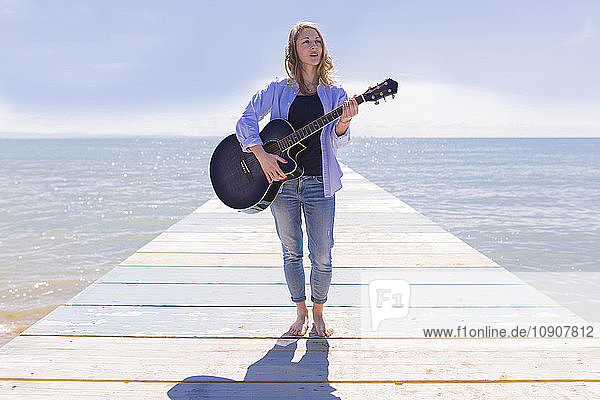 Young woman with guitar on jetty