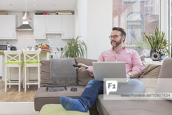 Mature man sitting on couch using laptop and remote control