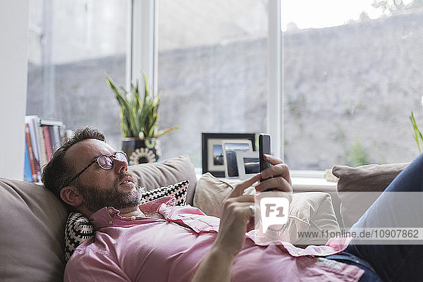 Mature mna lying on couch checking messages on smart phone