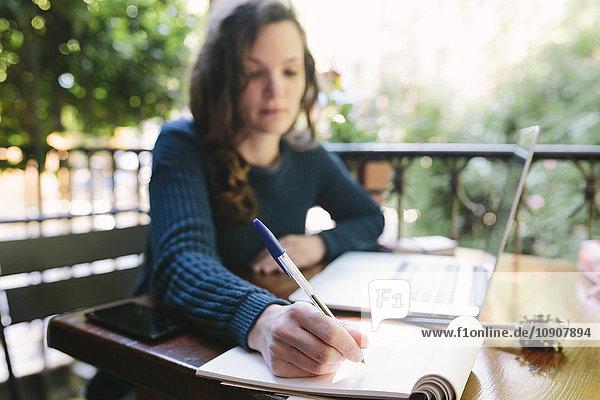 Junge Frau auf dem Balkon sitzend mit Laptop