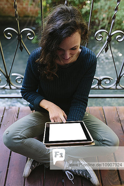 Young woman sitting on balcony  working with digital tablet