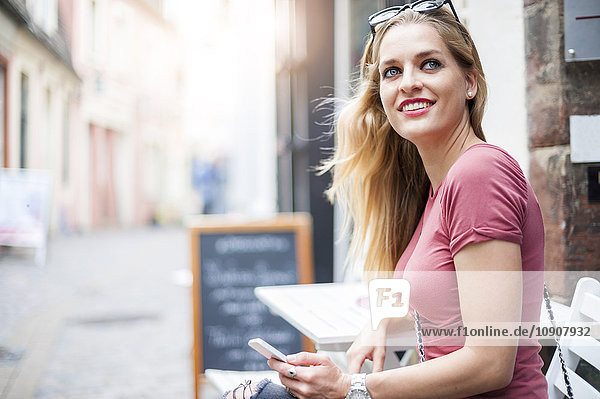Portrait of smiling woman with smartphone sitting in a sidewalk cafe watching something