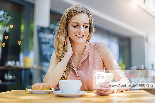 Portrait of smiling woman sitting in a sidewalk cafe looking at her smartphone