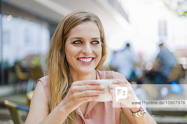 Portrait of smiling woman sitting in a sidewalk cafe with cup of coffee