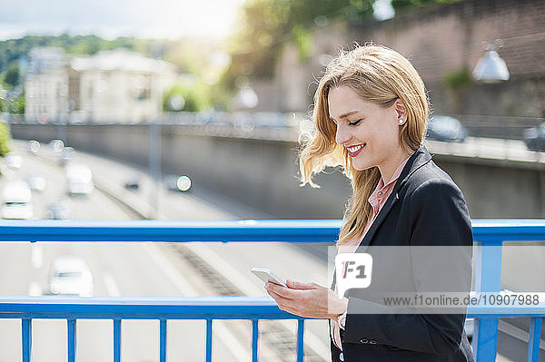 Smiling businesswoman on a bridge looking at her smartphone