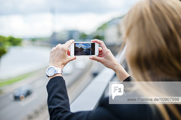 Back view of woman standing on a bridge taking photo with smartphone