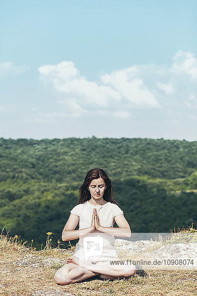 Young woman meditating on the cliff