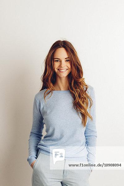 Porträt einer lächelnden jungen Frau mit Händen in der Tasche