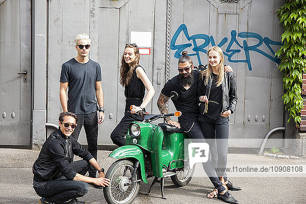 Group of five black dressed friends with green moped