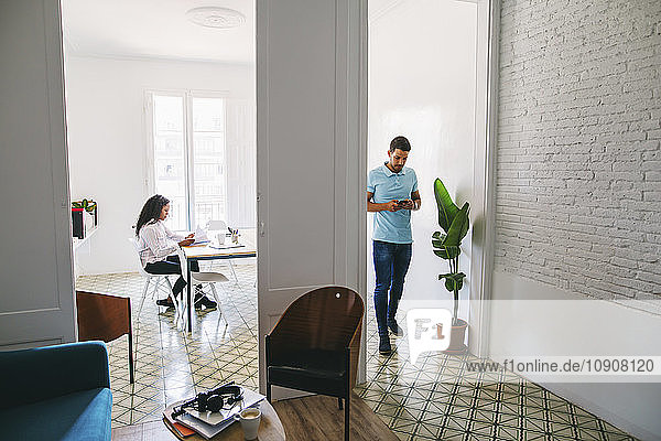 Young businessman and woman working in office