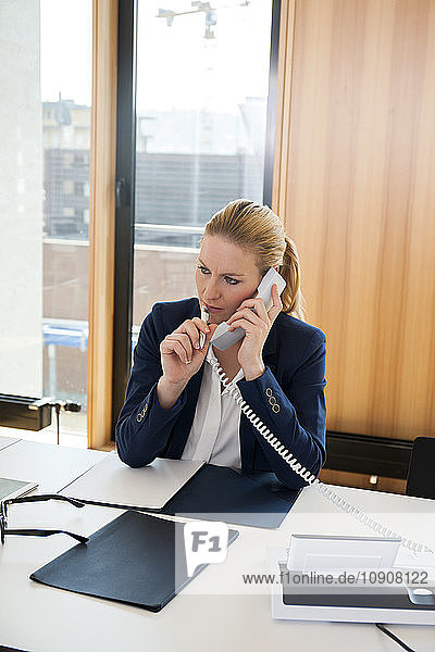 Businesswoman at office desk on the phone