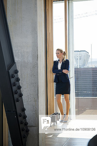 Businesswoman leaning against wall thinking