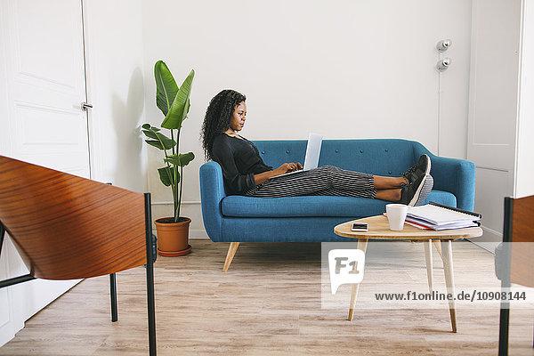 Geschäftsfrau sitzt auf der Couch im Büro mit Laptop