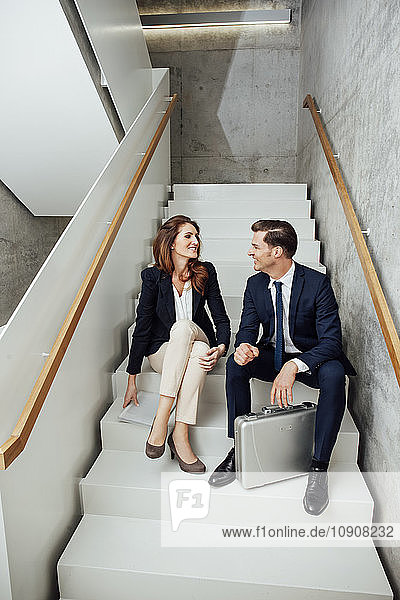 Two business colleagues sitting in staircase