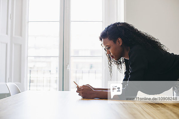 Young businesswoman in office checking messages